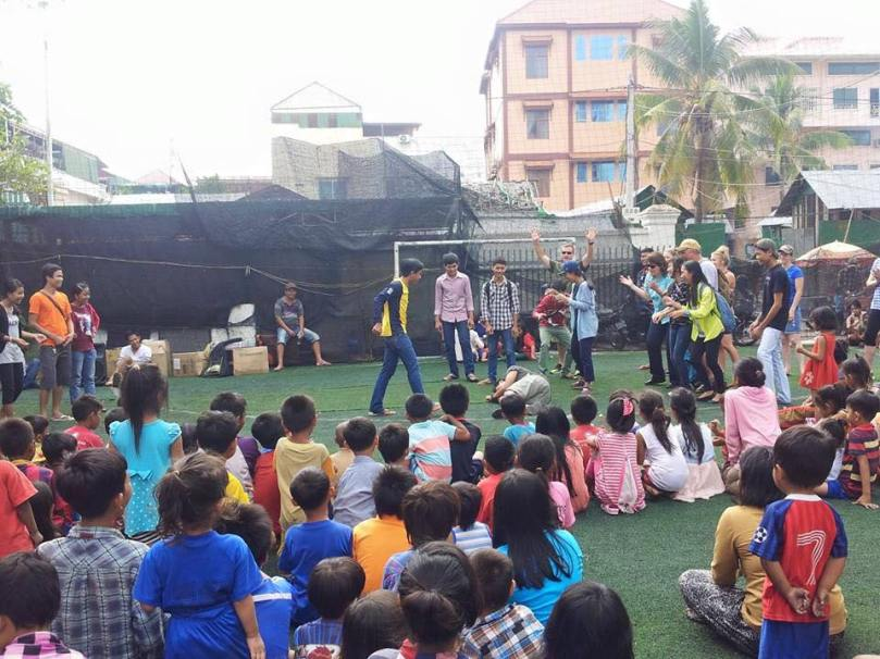 Slum outreach: Kids watch a skit of the story of David and Goliath (Goliath has just been slain and is lying on the ground.)