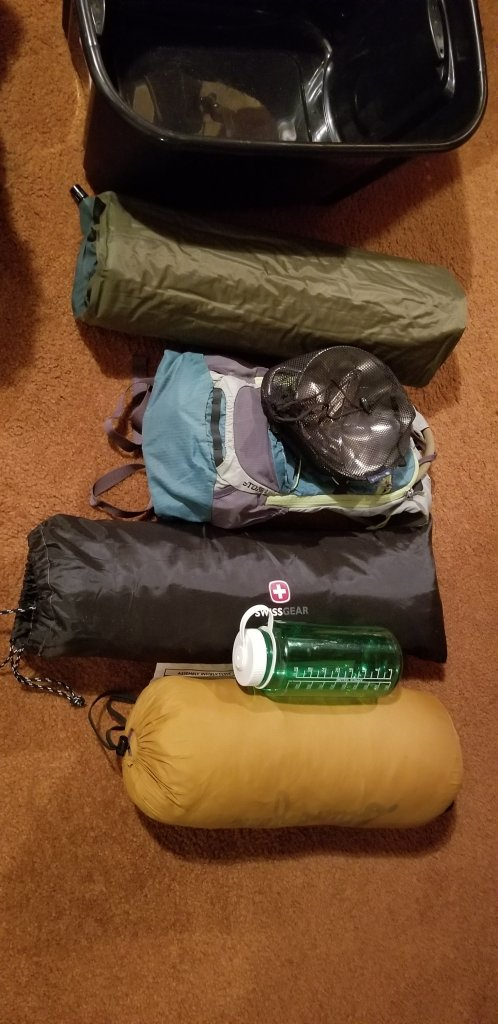 backpacking gear - tent, sleeping bag and pad, water pack and mess kit.